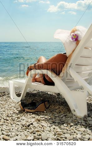 Closeup View On Lady In Chaise-longue At The Coast Of Sea
