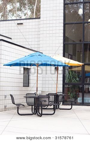 Patio Furniture At Outdoor Cafe With Blue And Yellow Umbrella