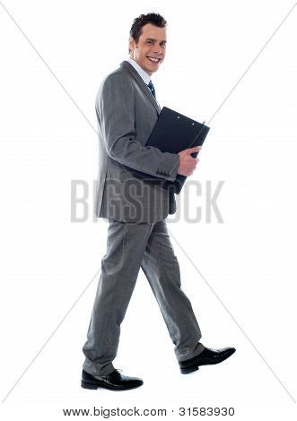 Businessman Holding Documents And Walking