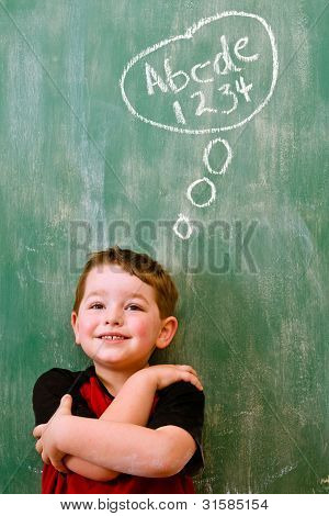 Education school concept of preschooler boy thinking about writing and math in front of chalkboard