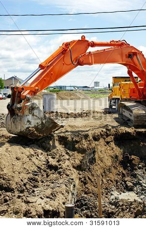 Orange Mechanical Digger And Hole