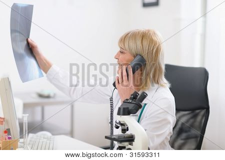Middle Age Doctor Woman Speaking Phone And Looking On Patients R