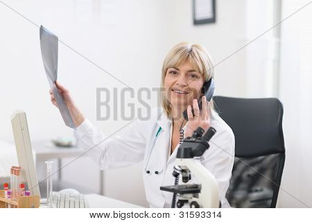 Middle Age Doctor Woman Holding Patients Roentgen And Speaking P