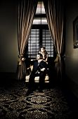 picture of snob  - Wealthy young retro couple posing before luxurious gold curtains for a portrait in their lavish family home in a depiction of fortune riches and wealth - JPG