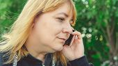 An Adult Woman Talking On A Smartphone, Close-up. Female Talking On Mobile Phone And Looking Away. B poster