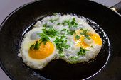 Sunny Side Up Fried Eggs With Parsley Decoration On Cast Iron Frying Pan. Concept Of Home Made Cuisi poster