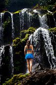 Young Traveler Woman Enjoying Waterfall Landscape. Caucasian Woman Standing On The Rock In Front Of  poster
