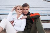 stock photo of bleachers  - happy male and female athletes sitting in the bleachers - JPG