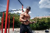 Fitness Man Training Chest With Resistance Bands At Street Gym Yard. Strength And Motivation. Outdoo poster