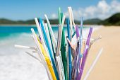 Heap Of Used Plastic Straws On Background Of Clean Beach And Ocean Waves. Plastic Ocean Pollution, E poster