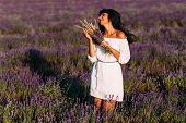 Beautiful Girl Is Among The Lavender Fields. Beautiful Girl At Sunset. The Girl On The Flower Field. poster
