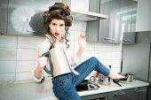 Beautiful girl is posing in everyday clothes with curlers in her hair and holding a kettle. Fashion  poster