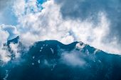 High Rocky Mountain Peak In The Clouds. Mountain Peak With Green Vegetation On The Slopes. poster