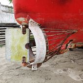 An Old Small Boat Propeller. Ship Propeller And Rudder. Wooden Fishing Boat On The Beach. Details Of poster