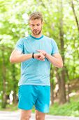 A Digital Sports Watch. Athletic Man Tracking Training With Watch On Hand. Handsome Athlete Using Sm poster