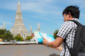 Man Stand Holding A Map And A Mobile Phone On The River And Wat Arun In Thailand. poster