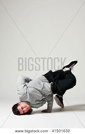 studio shot of cool breakdancer over grey background