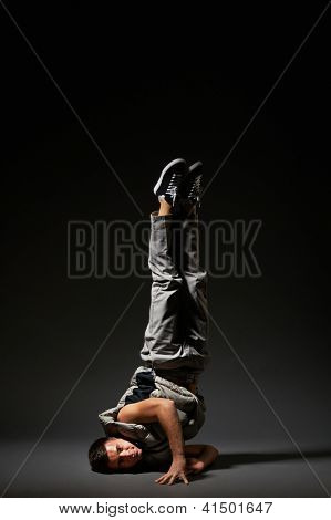 cool breakdancer standing in freeze. studio shot over grey background