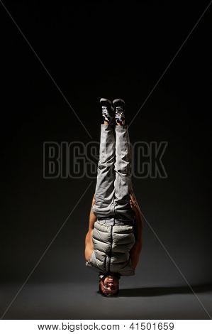 cool breakdancer standing on his head. studio shot over grey background