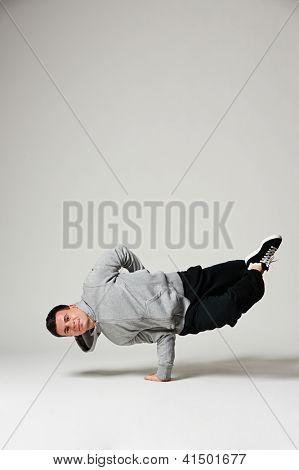 cool b-boy standing on one hand. studio shot over grey background