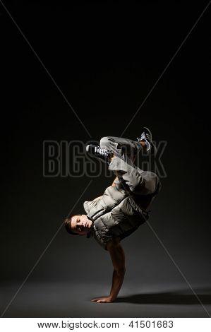 breakdancer standing on one hand. studio shot over dark background