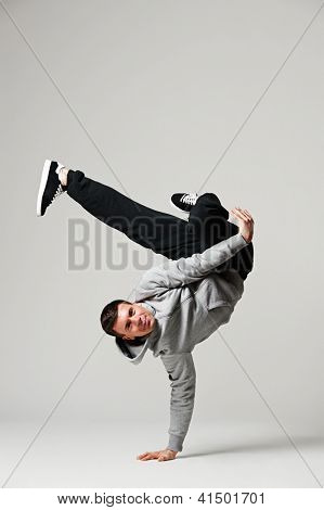 cool b-boy standing in freeze. studio shot over grey background