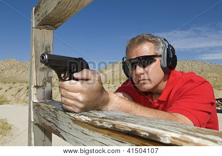 Mature man aiming with handgun at combat training