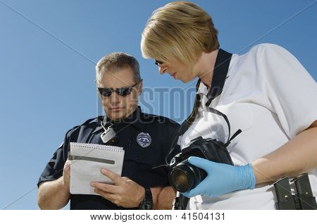 Low angle view of two police officers discussing report