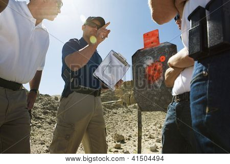 Instructor holding clipboard in front of group on shooting range
