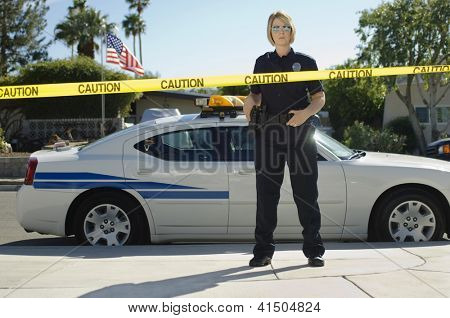 Police officer standing behind yellow caution tape by car