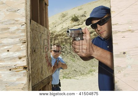 Two men aiming with handgun at combat training