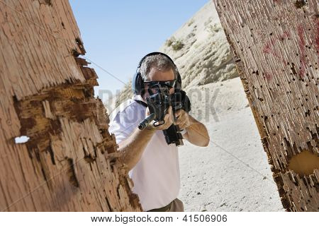 Mature man aiming with gun at combat training