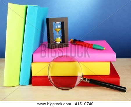 color books with magnifying glass on table on blue background