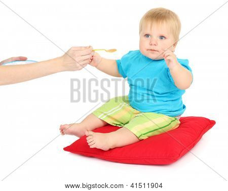 Little boy sitting on red pillow and eating applesauce, isolated on white