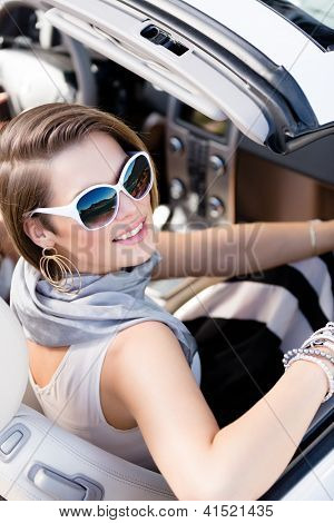 Pretty woman wearing sunglasses with white rim turns back sitting in the car