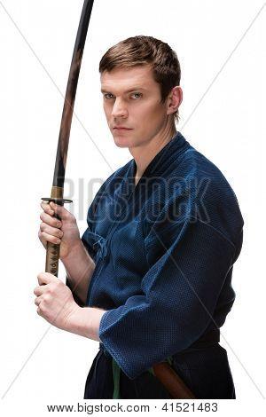 Kendoka in hakama hands bokken, isolated on white background. Japanese martial art of sword fighting