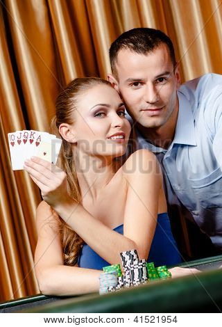 Couple playing poker at the gambling house. Woman keeps cards in hand