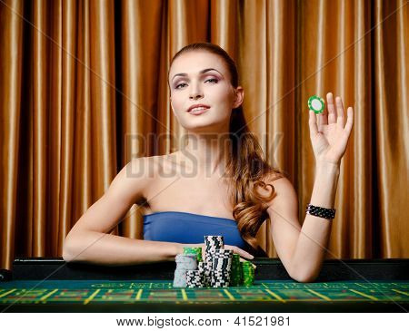 Portrait of the female gambler at the roulette table holding chip in the hand
