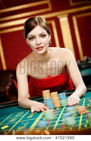 Playing roulette woman places a bet at the gambling house