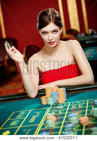 Girl gambles at the gambling house. Addiction to the playing roulette