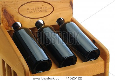 Closeup of a wine rack with three Cabernet Sauvignon bottles.