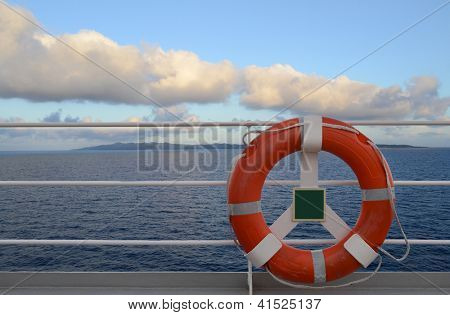 Life Preserver on a cruise ship railing with a tropical island in the distance.
