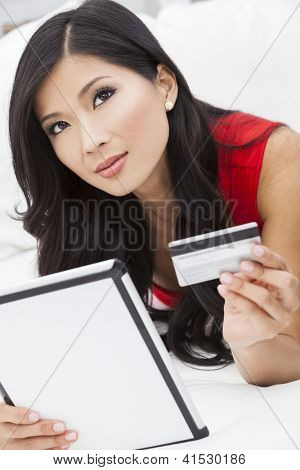 Beautiful Asian Chinese woman using a credit card to shop on the internet with a tablet computer