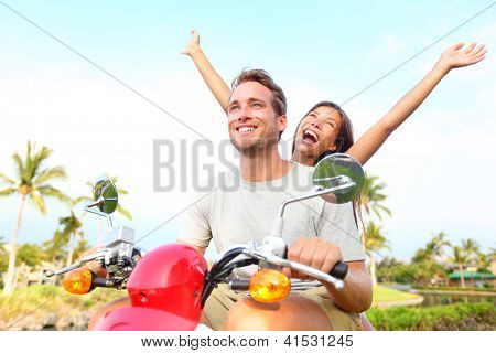 Happy free freedom couple driving scooter excited on summer holidays vacation. Young multiethnic couple, Asian woman, Caucasian man
