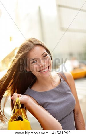 Shopping woman on Manhattan, New York City.  Shopper smiling happy outdoor in streets of New York. Fresh blissful mixed race Asian / Caucasian girl holding shopping bag with yellow taxi cab.