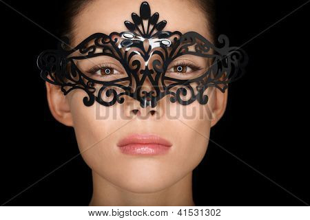 Mask. Beauty woman wearing carnival mask isolated on black background. Close up portrait of young mixed race Asian Caucasian girl hiding behind mask.