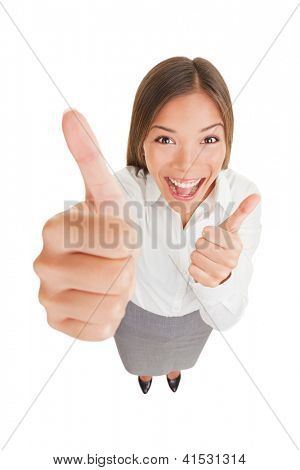 Happy excited woman giving thumbs up. Fun high angle view of laughing woman giving thumbs up with both hands showing enthusiasm isolated on white background in full length. Asian businesswoman.