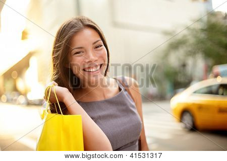 Shopping business woman on Manhattan, New York City. Fresh blissful mixed race Asian / Caucasian young professional  holding shopping bags outdoors in streets of New York