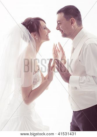 Bride And Groom Face to face Holding Hands Over White Background