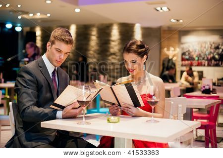young happy couple in restaurant reading menu